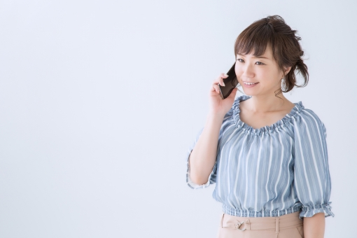 スマートフォンと女性(笑顔)の写真