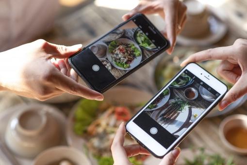 ベトナム料理レストランで料理を撮影するカップルの手元2の写真