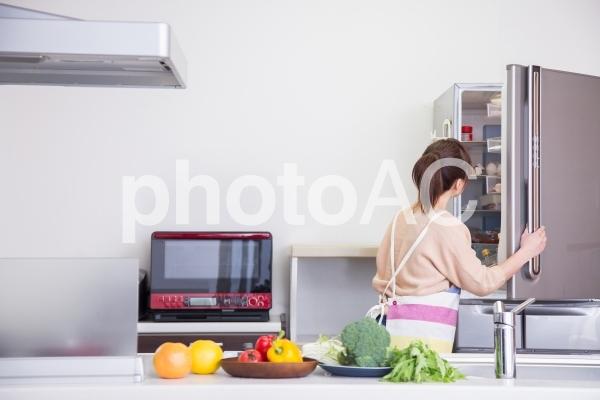 冷蔵庫を見る女性の写真