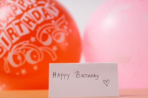 バースデーカード 紙 走り書き 手書き 直筆 ピンク レッド 赤 思いやり 真心 文字 誕生日 誕生祝 ハッピーバースデー 英語 テーブル ベージュ 木目 置く 物撮り 人物なし 室内 上から視線 複数 風船 ふうせん バルーン 2個 贈り物 プレゼント ギフト Happy Birthday