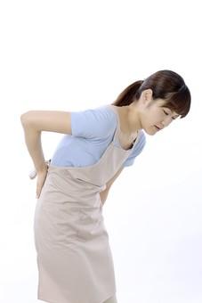 人物 屋内 白バック 白背景 日本人 1人 女性 20代 30代 エプロン  奥さん 奥様 婦人 家庭人 夫人 主婦 若い ポーズ 顔 表情 痛み 痛む 腰痛 腰 手 押さえる 押す さする 前屈み 苦痛 辛い 不調 mdjf018