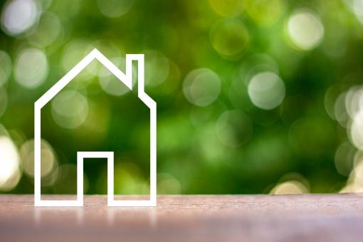 緑ぼかし背景と住宅模型の写真