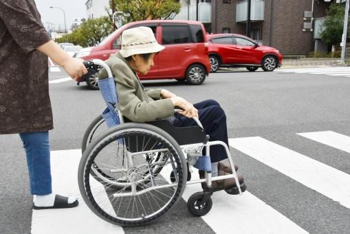 高齢者の介護 車椅子で横断歩道を渡る女性の写真