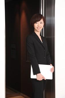 ビジネス 仕事 会社 ビル 建物 建築 建築物 壁 エレベーター 上下 乗る 降りる 開閉 開く 閉まる サラリーマン ビジネスマン 会社員 女性社員 女性 女の人 成人 20代 オフィス内 スーツ ポーズ 立つ 笑顔 持つ 室内 屋内 日本人 人物 ノートパソコン モバイル mdjf002