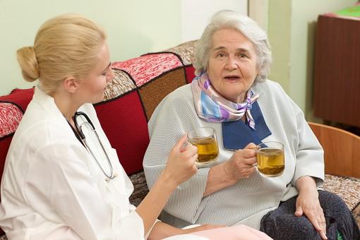 室内 屋内 外国人 老人 高齢者 女性 おばあさん おばあちゃん 患者 白髪 白人 女医 金髪 白衣 医師 医者 病院 病室 個室 家 自宅 ベッドルーム ソファー ソファ 座る お茶 カップ 飲む ハーブティー ティー 並ぶ 見守る 寄り添う 会話 話す しゃべる 訪問 訪問診療 mdff142 mdfs017