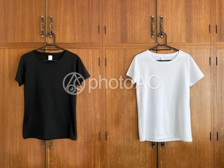 クローゼットの扉にかけられた黒と白のTシャツの写真