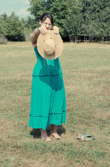 外国 海外 屋外 野外 自然 人物 1人 外国人 白人 セルビア人 大人 若い 女性 女 女の子 ブルネット 黒髪 セミロング まとめ髪 ひっつめ髪 無造作ヘア 普段着 青緑の服 ワンピース ロングワンピース ノースリーブ キャミソールワンピース ネックレス ペンダント レザーコード ブレスレット アクセサリー 眼鏡 メガネ めがね 帽子 麦わら帽子 裸足 はだし つま先 サンダル 植え込み 低木 木 木立 芝生 柵 空 mdff021