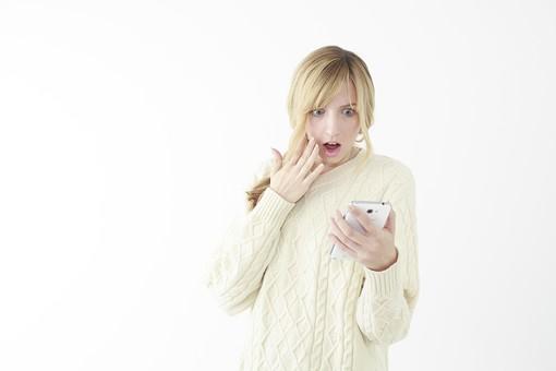 人物 女性 20代 外国人 外人  外国人女性 外人女性 モデル 若い セーター  ニット 私服 カジュアル ポーズ 金髪  ロングヘア 屋内 白バック 白背景 スマホ スマートフォン 電話 見る 驚く びっくり ビックリ 表情 上半身 mdff045