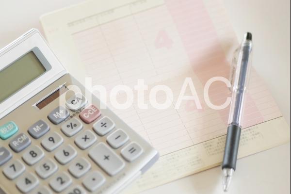 通帳と電卓とボールペンの写真
