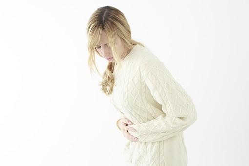 人物 女性 20代 外国人 外人  外国人女性 外人女性 モデル 若い セーター  ニット 私服 カジュアル ポーズ 金髪  ロングヘア 屋内 白バック 白背景 お腹 押さえる 腹痛 痛い 体調不良 下を向く 俯く  横向き mdff045