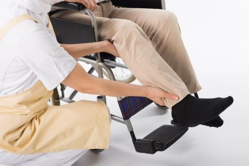 老人 高齢者 お年寄り シニア 男性 おとこ 男 女性 おんな 女 2人 二人 手 両手 介護士 看護師 エプロン  介護 不自由 椅子 ヘルパー 白バック 白背景 車いす 車椅子 白 シャツ 立つ  座る   ベージュ 茶色 足 足元  見る 手 添える