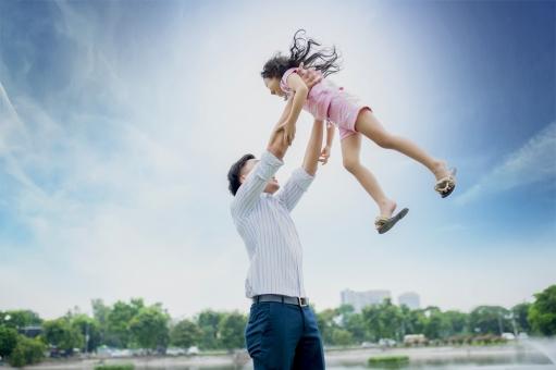 娘を抱っこするアジア人のお父さん2の写真