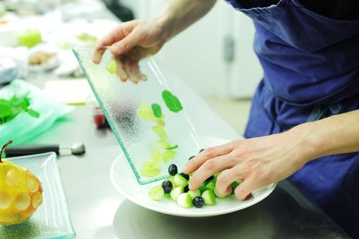 厨房 台所 キッチン 料理 調理 レストラン シェフ コック 料理人 女性 外国人 デザート フルーツ 果物 メロン ブルーベリー ミント マスカット グリーン お皿 白 緑 青 ガラス 盛りつける のせる 細い手 華奢