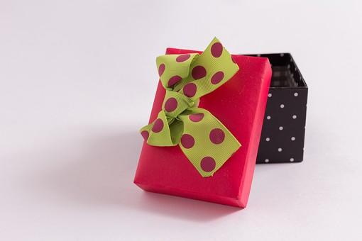 プレゼント 贈り物 水玉 ドット リボン 黄色 イエロー 赤 レッド 黒 ブラック ギフト 贈答品 原色 印象的 おくり物 1個 箱 屋内 人物なし 物撮り 包装紙 紙 置く 横から視線 接写 アップ ズーム 斬新 現代的 若者 かわいい 蓋 ふた 開ける