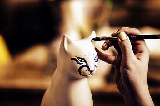 陶芸 工芸 伝統 手作り 技 職人技 芸術 アート 置物 美術品 焼き物 陶器 素焼き アップ ネコ 猫 ねこ 絵付け 色塗り おしゃれ きれい かわいい 物撮り インテリア 青 青色 ターコイズ 窓越し 手 手元 アップ 筆 絵筆 工房 アトリエ