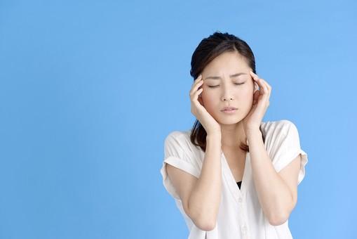女性 ポーズ 人物 30代 日本人 黒髪 爽やか カジュアル 屋内 正面 ブルーバック 青背景 半そで 白  上半身 痛い こめかみ 手を当てる 我慢 頭痛 痛み 疲労 疲れる 目 瞑る 憂鬱 不安 鈍痛 両手 mdjf013