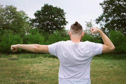 人物写真 ポートレート ポートレイト 人物 人 人間 外国人  男性 白人男性  フィットネス 運動 ストレッチ アウトドア  野原 木 草 葉 自然  後姿 背中 首 うなじ 頭  Tシャツ  結う 腕 伸ばす 落ち着き リラックス 健康 二の腕 筋肉 mdfm006