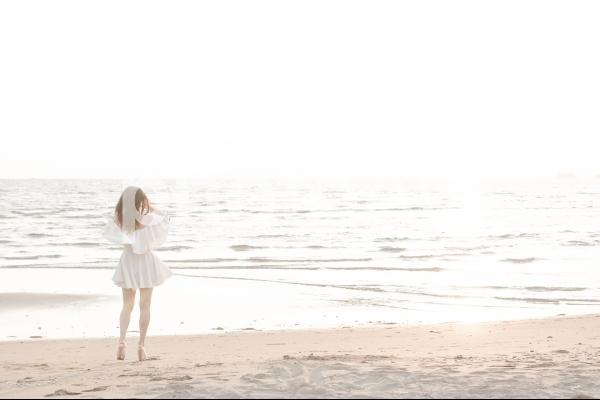 海辺を歩く白いワンピースの女性の写真