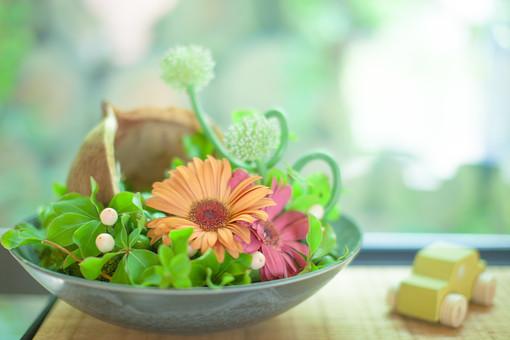 自然 植物 葉 葉っぱ 緑 花 花びら つぼみ オレンジ色 橙色 赤色 飾る ディスプレイ フラワーアレンジメント 皿 器 入れ物 入れる 盛る 車 ミニカー おもちゃ ぼやける ピンボケ 机 テーブル 無人 アップ 加工 景観 幻想的