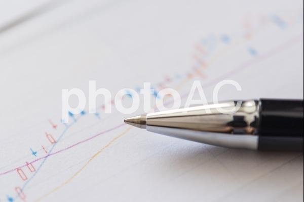 株価のチャートとボールペンの写真