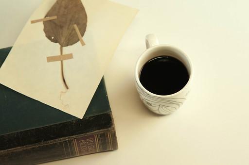 本 ブック 書物 書籍 図書 読書 読む 趣味 勉強 リラックス 寛ぐ くつろぐ コーヒー マグカップ カップ コップ 飲み物 ドリンク 接写 クローズアップ テーブル 机 しおり 葉 葉っぱ 押し花 植物 背表紙 厚い 分厚い 置く 乗せる 乗る 上に置く
