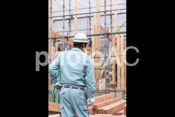 建設工事中の新築住宅の木の柱を見守る現場監督の写真