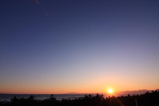 海 海岸 海辺 浜辺 空 青 オレンジ 朝 朝焼け 夕日 夕暮れ 夕焼け 黄昏 暗い 寂しい 終わり 始まり 水平線 波 さざ波 リラックス ナチュラル グラデーション 自然 リゾート 保養地 散歩 余白 湘南 植物 繁み 太陽 山 丘陵 陸地 逆光