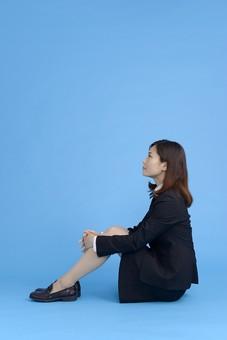 人物 女性 日本人 20代 若者  ビジネス スーツ 黒 紺色 セミロング  OL 社会人 会社員 ビジネスマン 就活  就職活動 真面目 ポーズ 屋内 スタジオ撮影  ブルーバック  全身 横向き 横顔  座る 膝を抱える 体育座り 見つめる mdjf013