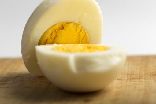 たまご 卵 玉子 タマゴ エッグ 卵色 料理 食べ物 食材 食料 物撮り 屋内 人物なし 横から視線 レシピ 鶏 にわとり ニワトリ ボイル ゆで卵 黄身 白身 白バック 床 木 木目 白 黄 2切れ アップ ズーム 接写