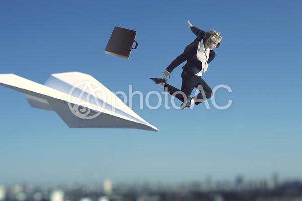 紙飛行機と飛ぶビジネスマンの写真