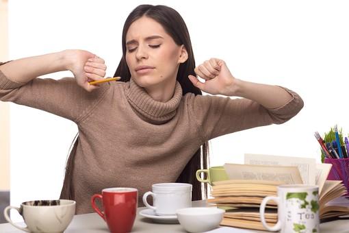 屋内 人物 外国人 女性 1人  大人 20代 30代 セーター 茶色 机 本 カップ マグカップ 飲み物 複数 仕事 学習 勉強 ビジネス  ビジネスウーマン 若い 座る 伸び 腕 伸ばす 持つ 筆記用具 表情 疲労 疲れ 眠い やれやれ 目 閉じる うーん 睡眠不足 飲み物 女 人 室内 白バック 白背景 mdff127