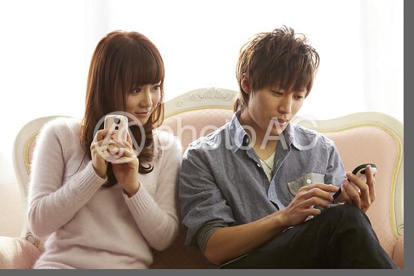 携帯を見るカップル16の写真