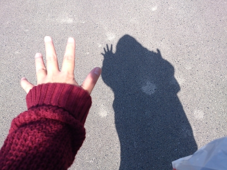 影 シルエット 人物 ジャンケン パー 手の平 指 パーツ 手 コンクリート 影絵 映す 光 人間 一人 赤 セーター ニット 爪 秋 冬 素朴 情景 情緒 回想 懐かしい 思い出 散歩 散策 ぶらり