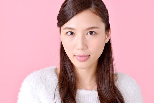 人物 女性 日本人 若者 若い  20代 美人 かわいい ロングヘア カジュアル  ラフ 私服 セーター ニット 屋内  スタジオ撮影 背景 ピンク ピンクバック ポーズ  おすすめ 顔 表情 舌 舌を出す あっかんべー あかんべえ mdjf007