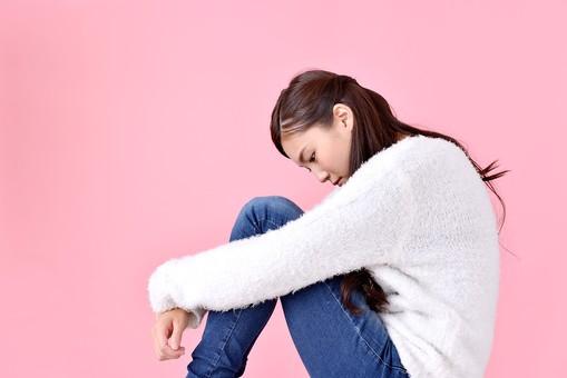 人物 女性 日本人 若者 若い  20代 美人 かわいい ロングヘア カジュアル  ラフ 私服 セーター ニット 屋内  スタジオ撮影 背景 ピンク ピンクバック ポーズ  おすすめ 座る 膝を抱える 落ち込む ショック 気落ちする しょんぼり 憂鬱 孤独 横向き 横顔 mdjf007