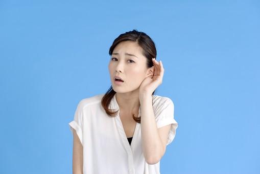 女性 ポーズ 人物 30代 日本人 黒髪 爽やか カジュアル 屋内 正面 ブルーバック 青背景 半そで 白  両手 上半身 耳 手をやる 聞き返す 疑問 疑念 不安 遠い わからない 聞こえない 不明 mdjf013