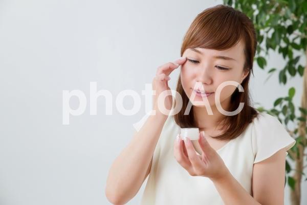 目尻にクリームを塗る女性の写真