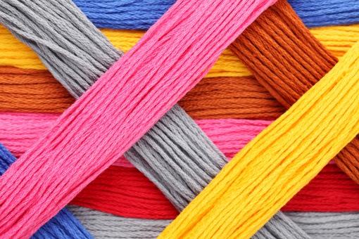 糸 裁縫糸 木綿糸 木綿 裁縫 ファッション 手芸 ソーイング 刺繍糸 紐 カラフル 色とりどり 鮮やか 趣味 工芸 洋裁 縫う 縫製 模様 配置 クローズアップ 裁縫材料 色 質感 テクスチャ テクスチャー 背景 バックグラウンド 素材 イメージ 一面 全面 交差 束 重なる 重ねる 重なり 無人 赤色 黄色 青色 ピンク色 茶色 アップ