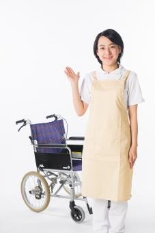 m女性 おんな 女 エプロン 白衣 ベージュ 車椅子 車いす 介護 介護士 介助 ナース 病院  ヘルパー 看護師 笑顔 微笑み 手 上げる 白 白背景 白バック 立つ 爽やか 優しい 穏やか 案内 説明 どうぞ  mdjf017