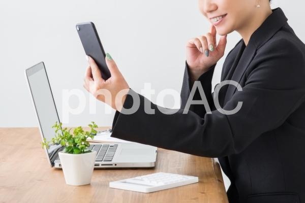 スマートフォンを見る女性(笑顔)の写真
