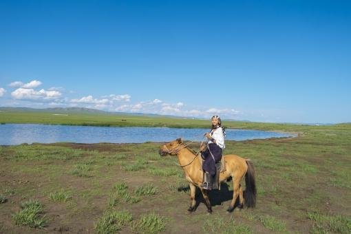 モンゴルで馬に乗る女性の写真