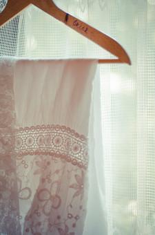 結婚 結婚式 挙式 幸せ お祝い 女性 女の人 新婦 花嫁 妻 服 洋服 ドレス ウェディングドレス レース 模様 透ける ピンク 桃色 白 ホワイト ハンガー 木製 かける カーテン 格子 隙間 光 太陽光 陽光 陽射し 窓 窓辺 室内 屋内