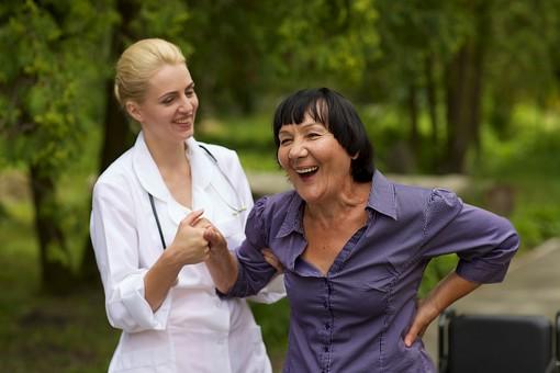 屋外 野外 外 病院 庭 公園 外国人 老人 高齢者 女性 おばあさん おばあちゃん 患者 女医 白人 金髪 白衣 医師 医者 スカート 車椅子 車いす 乗る 座る 散歩 歩く 立ち止まる 止まる 立つ 立たせる 立ち上がる 立ち上がらせる 手を持つ 手を引く 助ける 介助 介護 手伝う 笑顔 笑う mdfs016 mdff142