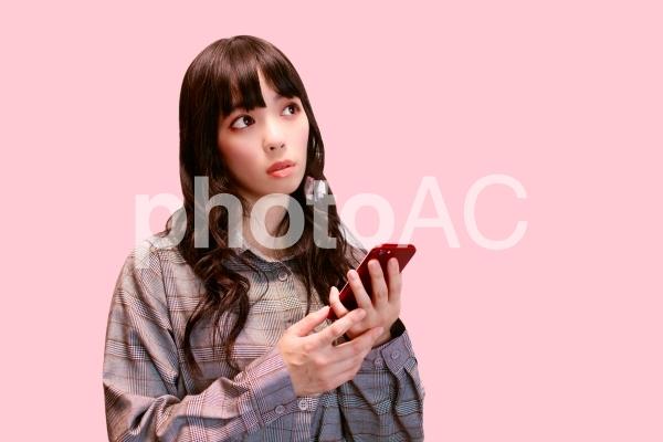 スマホを持ち考える女性の写真