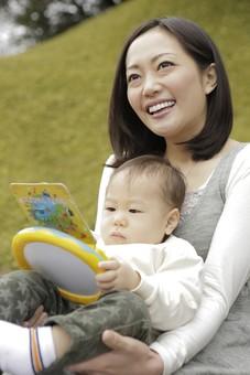 親子 母子 親 おや 母 母親 ママ マザー 子ども 子供 子 赤ちゃん 赤ん坊 乳児 幼児 ベイビー 抱っこ だっこ 抱く 絆 笑顔 笑う 女性 女 人物 触れ合い ふれあい バストアップ 上半身 公園 草原 おもちゃ 玩具 座る 日本人 mdfk008 mdjf016