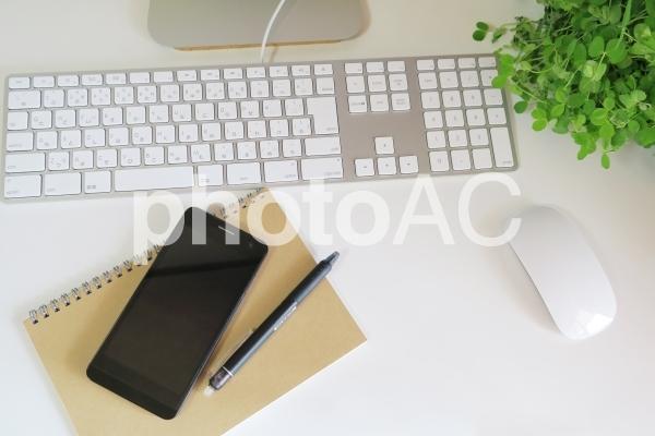 パソコンとスマートフォンの仕事場の写真