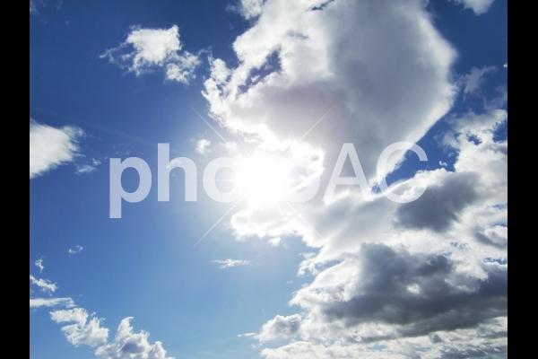 雲の切れ間から光が射す空の写真