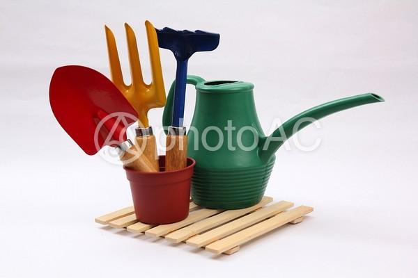 スコップとレーキと植木鉢とジョウロの写真