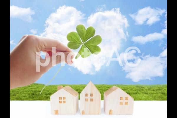 四葉のクローバーを持つ男性の手とハート型の雲と家の写真