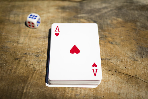 トランプ カード ゲーム 札 娯楽 木 屋外 茶色 机 テーブル 赤 青 A 1 エース ハート 絵札 黒 木目 手品 マジック 遊び 絵札 乱雑 サイコロ  重ねる 配る 切る カードゲーム